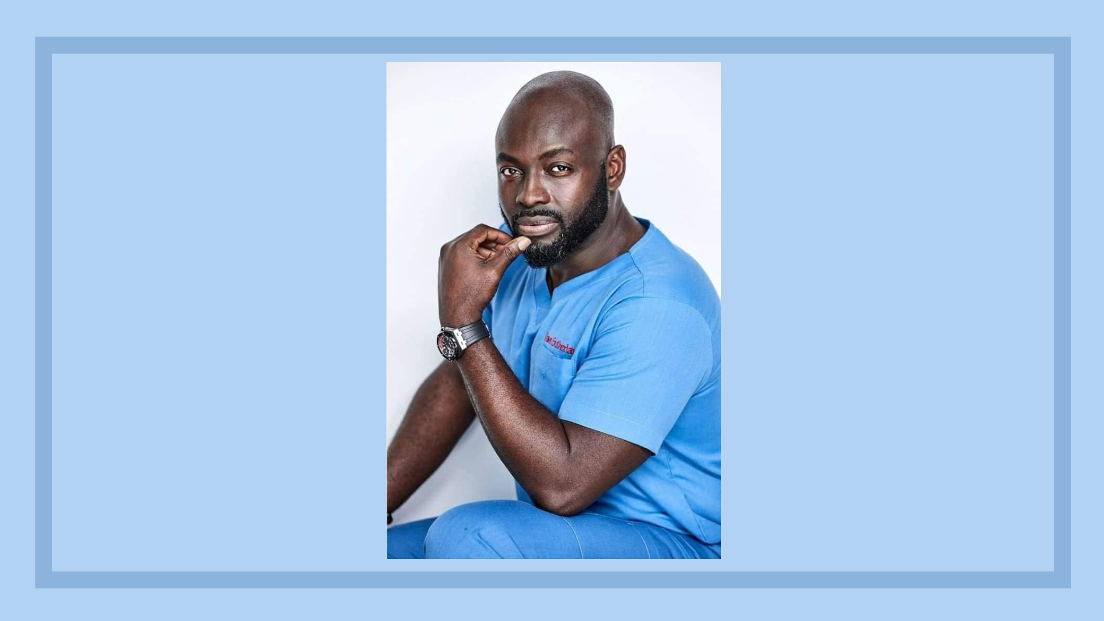 Dr. Michael K. Obeng seated wearing blue with hand under chin,